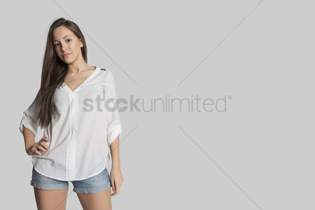 Three quarter length : Portrait of confident girl in hot pants posing against gray background
