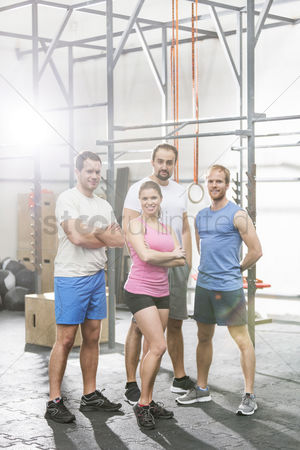 Muscle training : Portrait of confident people standing at crossfit gym