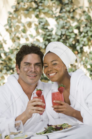 Toasting : Portrait of couple in bathrobes drinking at health spa