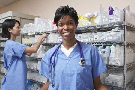 Medical : Portrait of female doctor nurse standing by shelves with medical supplies in background