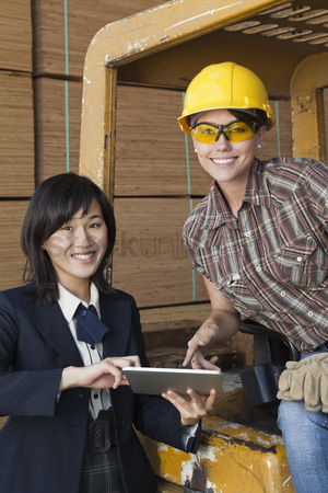 Forklift : Portrait of female inspector and industrial worker using tablet pc