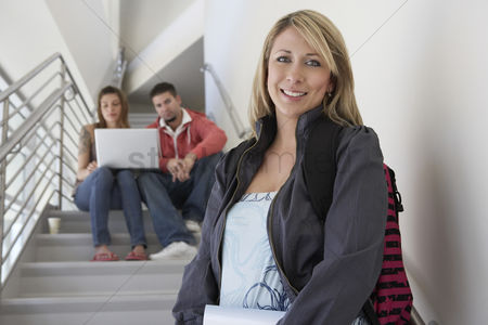 Steps : Portrait of female student on stairs friends using laptop in background