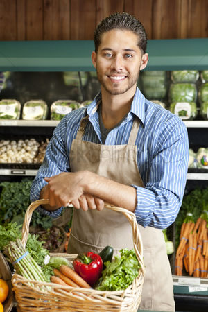 Supermarket : Portrait of handsome young salesperson standing with basket full of vegetables