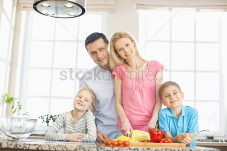 Three quarter length : Portrait of happy family preparing food in kitchen