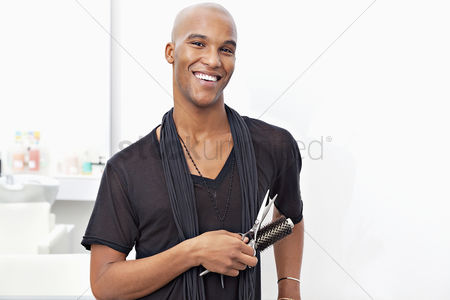 Smile : Portrait of happy male stylist holding hairbrush and scissors