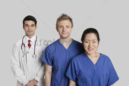Asian : Portrait of happy medical team standing over gray background