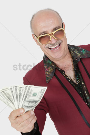 Man suit fashion : Portrait of happy senior man showing us banknotes against gray background
