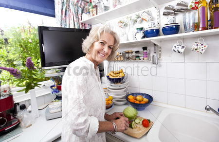 Retirement : Portrait of happy senior woman chopping fresh vegetables at kitchen counter