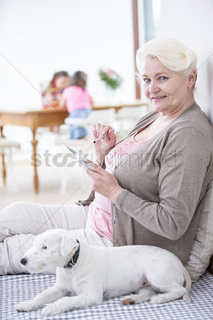 Domesticated animal : Portrait of happy senior woman using digital tablet by dog at home