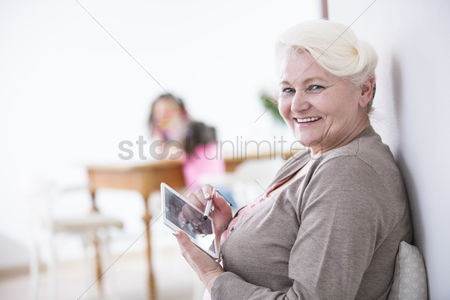Czech republic : Portrait of happy senior woman using digital tablet with stylus at home