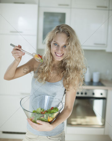 Czech republic : Portrait of happy woman mixing salad in kitchen