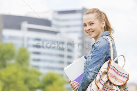College : Portrait of happy young female student at college campus