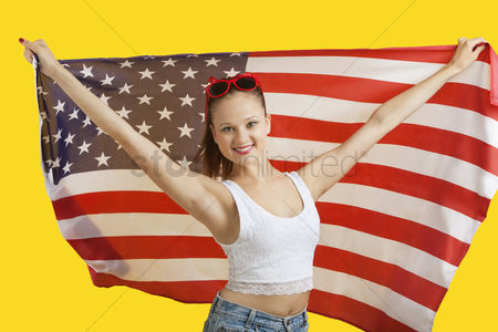 Flag : Portrait of happy young woman holding american flag over yellow background