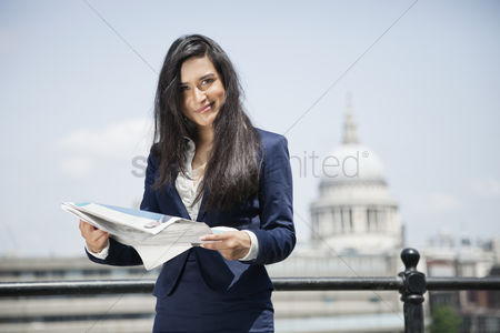 Asian : Portrait of indian businesswoman holding newspaper with st  paul s cathedral in background