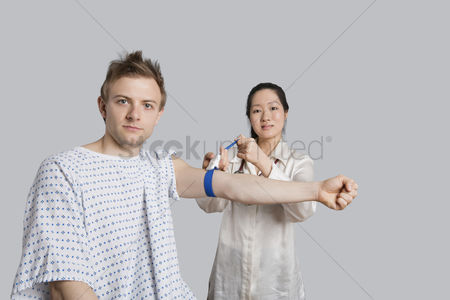 Examination : Portrait of male patient with doctor preparing him for a blood test
