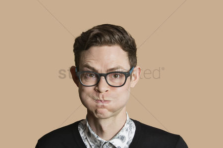 Funny : Portrait of mid adult man puffing cheeks over colored background