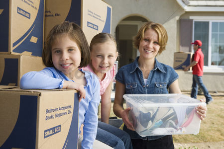 Group portrait : Portrait of mother with two daughters  6-9  by cardboard boxes