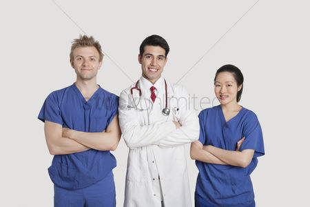 Asian : Portrait of multi ethnic healthcare professionals standing with arms crossed over gray background