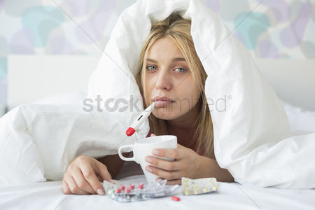 Medication : Portrait of sad woman with coffee mug taking temperature while wrapped in quilt on bed
