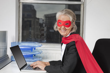 Office worker : Portrait of senior businesswoman in superhero costume using laptop at office desk