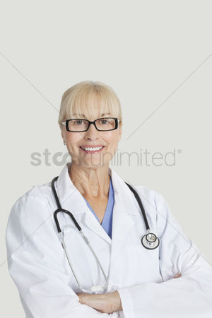 Senior women : Portrait of senior female doctor with arms crossed over gray background