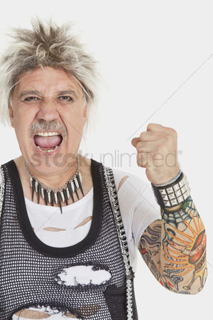 Funny : Portrait of senior male punk screaming with clenched fist over gray background