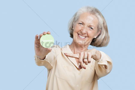 Blue background : Portrait of senior woman holding volunteer badge against blue background
