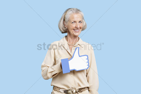 Senior women : Portrait of senior woman in casuals holding fake like button against blue background