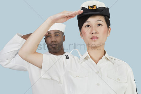 Respect : Portrait of serious female us navy officer and male sailor saluting over light blue background