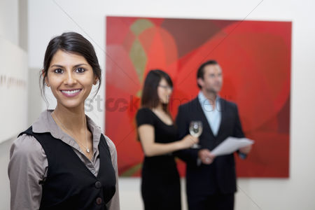 Interior background : Portrait of smiling young woman in front of a couple in art gallery