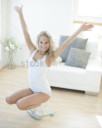 Czech republic : Portrait of successful woman crouching on weighing scale