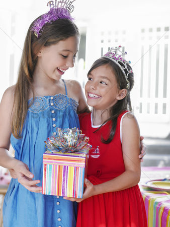 Birthday present : Portrait of two girls  7-9 10-12  in tiaras holding present smiling