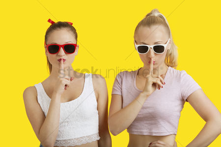 Ponytail : Portrait of two playful young women with fingers on lips over yellow background