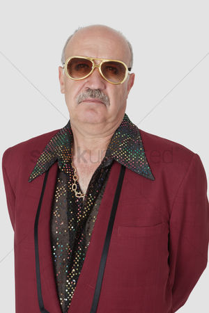 Man suit fashion : Portrait of unhappy senior man wearing sunglasses against gray background