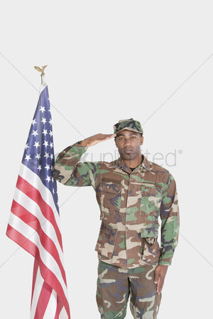 Respect : Portrait of us marine corps soldier saluting american flag over gray background