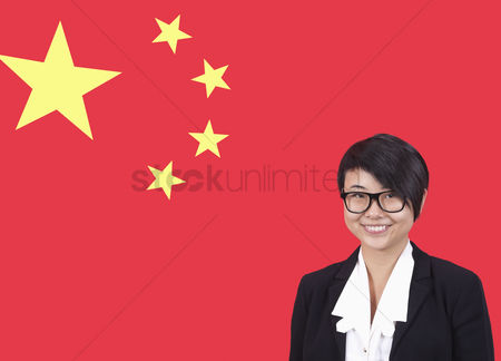 Respect : Portrait of young businesswoman smiling over chinese flag