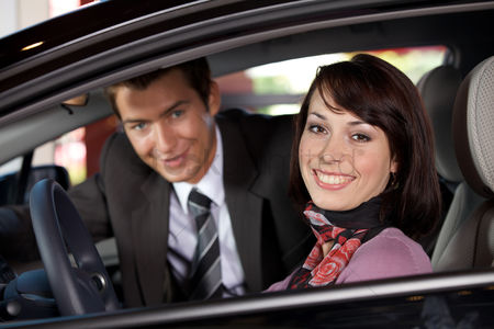 Car : Portrait of young couple sitting in a new car at showroom