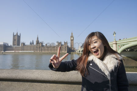 England : Portrait of young woman gesturing v-sign against big ben at london  england  uk