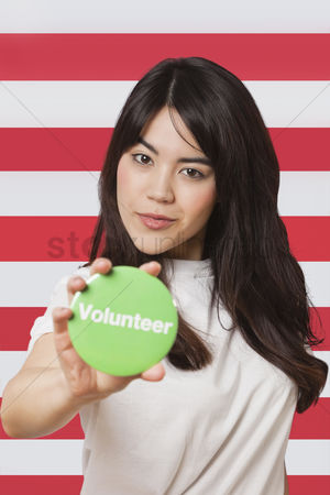 British ethnicity : Portrait of young woman holding out volunteer badge against american flag