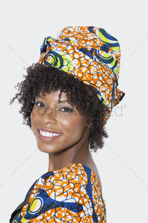 Traditional clothing : Portrait of young woman in african print attire looking over shoulder against gray background