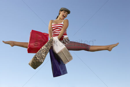 Shopping : Portrait of young woman jumping with shopping bags