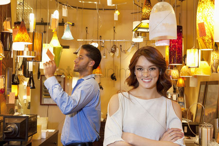 Variety : Portrait of young woman with arms crossed while man looking at price tag in background in lights store