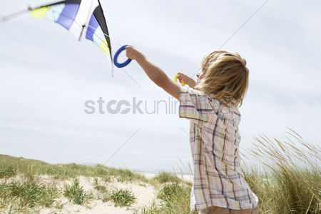 Children playing : Pre-teen boy arms raised flying kite on windy beach side view