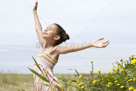 Arm raised : Pre-teen girl standing beside flowers eyes closed arms outstretched side view