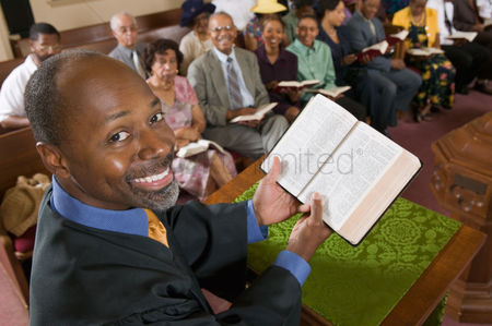Religion : Preacher at altar holding open bible in front of congregation portrait high angle view