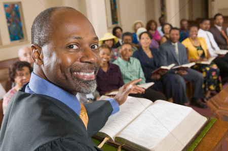 Religion : Preacher at altar with bible preaching to congregation portrait close up