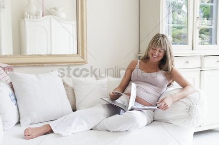 Interior : Pregnant woman reclining on sofa with book