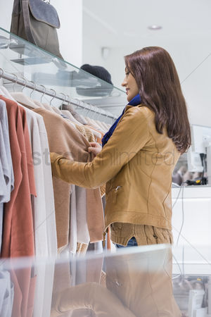 Shopping background : Profile shot of woman selecting sweater in store