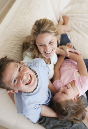 Sitting on lap : Raised view of laughing brother and sister piled on mother s lap with son smiling up to camera