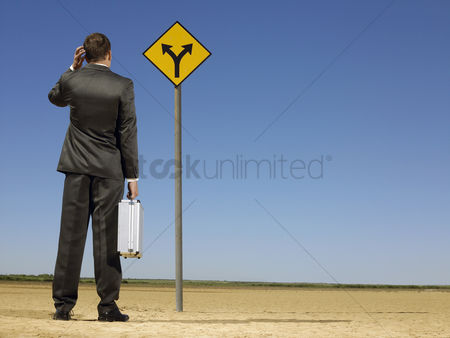Mid adult man : Rear view of confused businessman looking at desert road sign